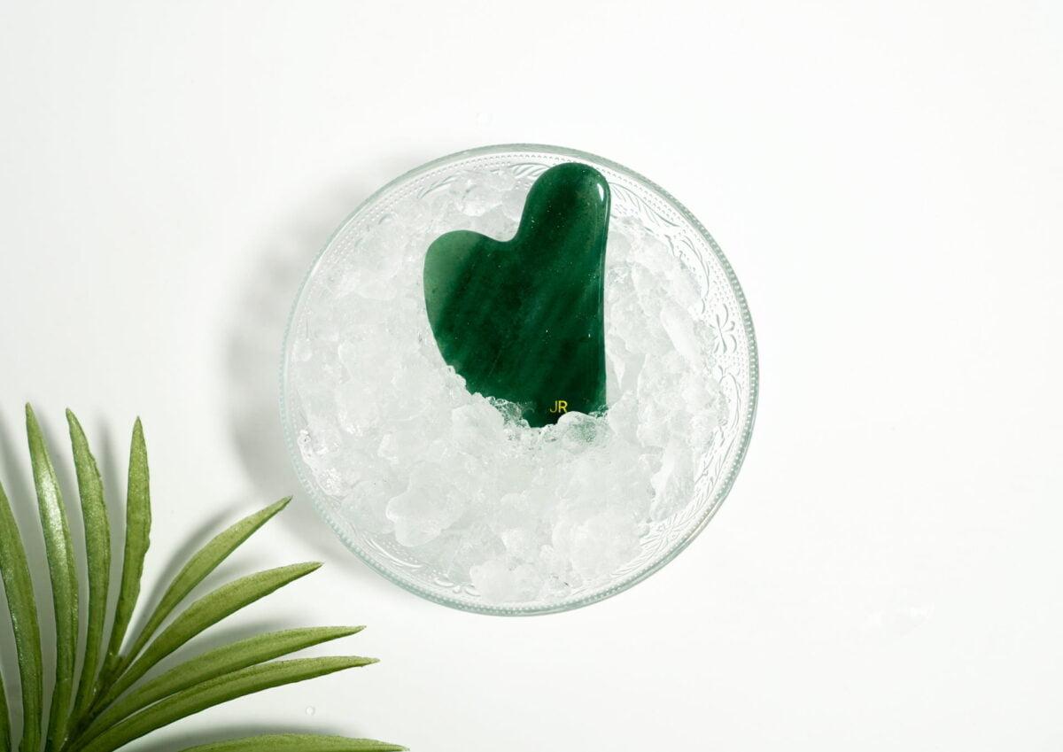 gua sha en jade frais dans des glaçons